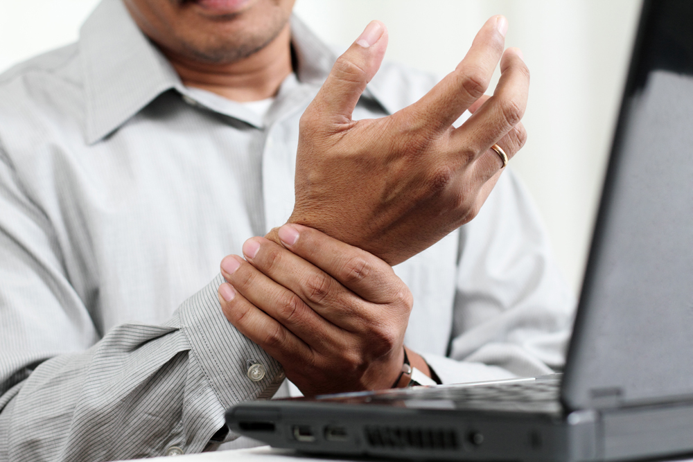 man suffering from carpal tunnel during work